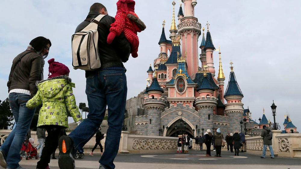 visitors-walk-towards-the-sleeping-beauty-castle-during-a-visit-to-the-disneyland-paris-resort-in-marne-la-vallee_5395589
